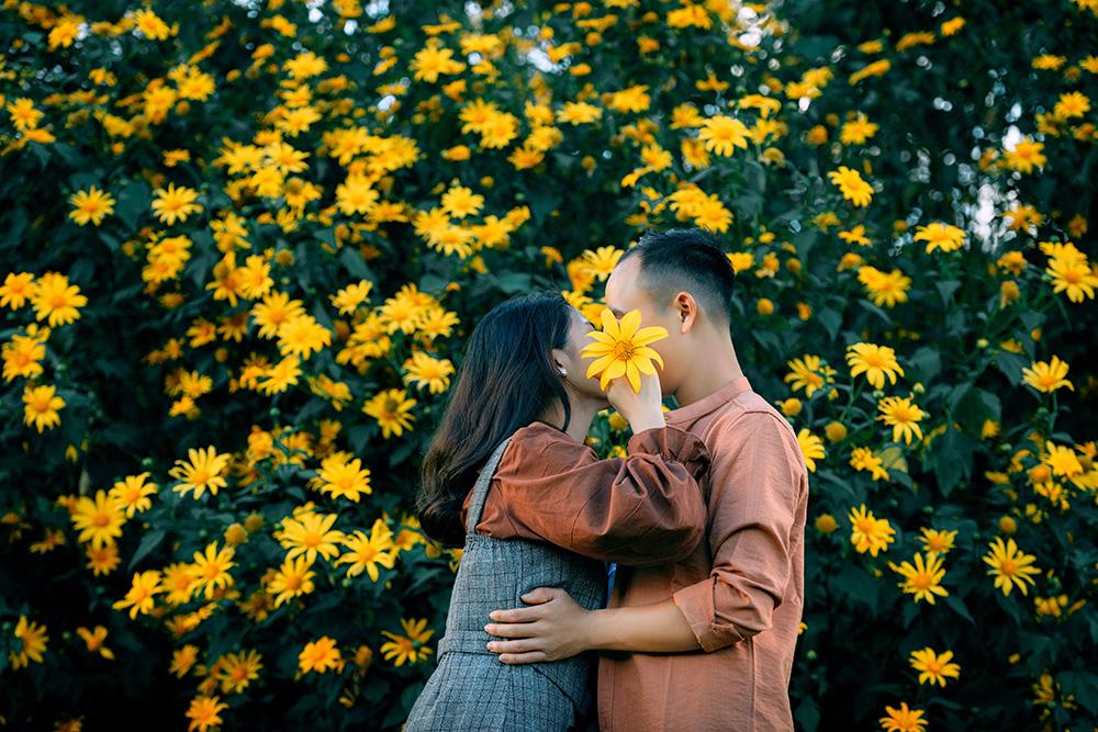 cuplu sarutandu-se langa flori